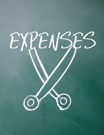 expenses cut sign on blackboard Stock Photo
