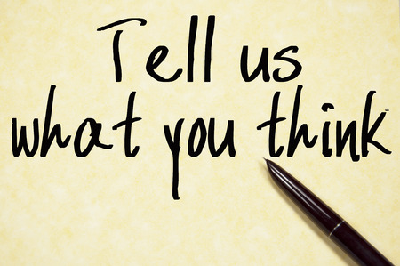 write us: tell us what you think text write on paper
