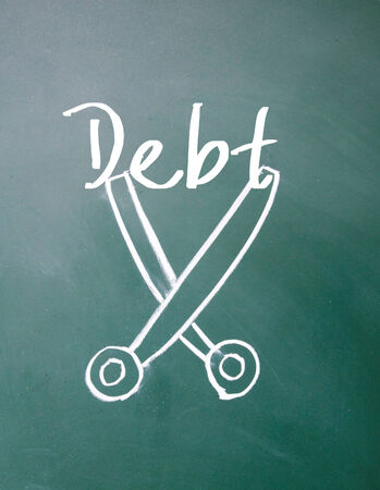 cost reduction: debt sign on blackboard Stock Photo