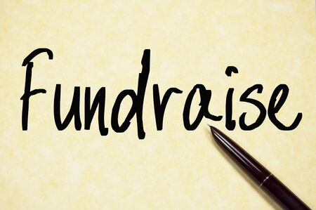 charity drive: fundraise word write on paper