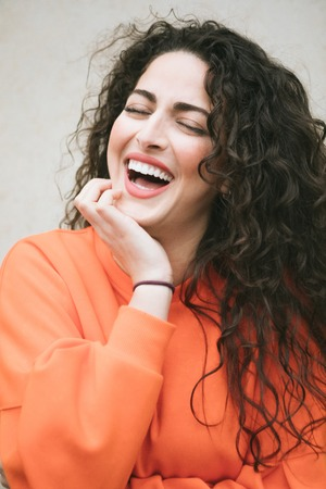 laughing friandly attractive girl oriental appearance. Active and exciting beauty. Long healthy curly hair.
