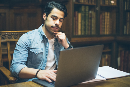Young arabic man working with laptop in library Standard-Bild
