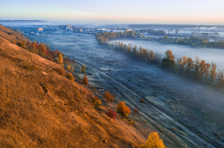 Autumn dry grass hill and foggy blue valley. Sunrise. City at the background.