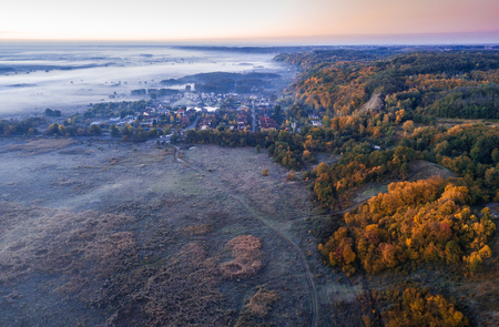 Early cold morning. Fog and frost. Small town village surrounded by hills and plain. Aerial drone photo