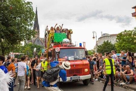 Berlin, Germany - June 9, 2019: Carnival of Cultures Parade Karneval der Kulturen Umzug - a multicultural music festival in Kreuzberg. Woman on truck performing. kirche am sudstern on the background. equal rights. photographer journalist in the foreground