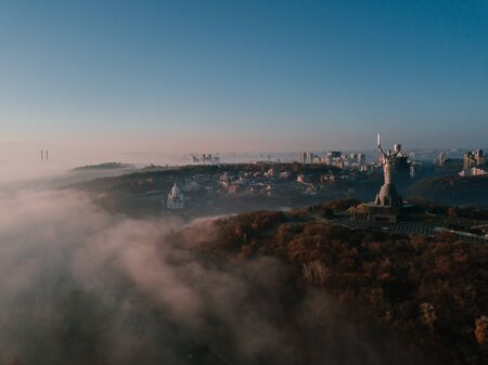 The Motherland Monument. Kiev Ukrainian capital popular tourist places to visit. Aeriel drone photo from the top. Foggy autumn morning in Kiev 新闻类图片
