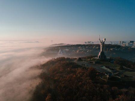 KKiev Ukraine The Motherland Monument USSR heritage. City hills on fog. Beautiful autumn morning. Aerial drone photo.