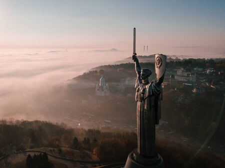 huge steel statue of woman with shield and sword The Motherland Monument in Kiev Ukraine. USSR heritage. Aeriel drone photo. 新闻类图片