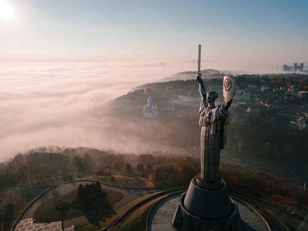 Kiev Ukraine the most popular tourist places to visit The Motherland Monument. Aerial drone photo of huge steel statue of woman with shield and sword. Cold foggy beautiful autumn morning