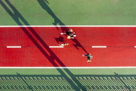 marathonlopers met hond. Sportieve levensstijl. Actief paar op rode en groene brug. Blijf fit motivatie. Luchtdrone bovenaanzicht