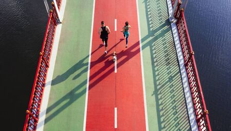 Aerial sport marathon. Couple running on the bridge wit small cute dog. Red and green colors. champions challenge. Keep fit motivation