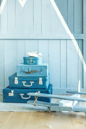 Boy room decoration. Blue Suitcases on the floor in the nursery kids room. Interior for child young pilot. Vertical composition