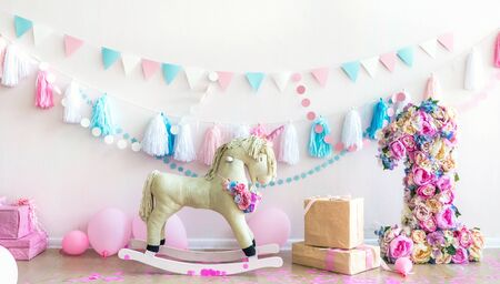 pink kids girly room with horse toy and flowers. Kids interior wall. Horizontal composition. Daylight