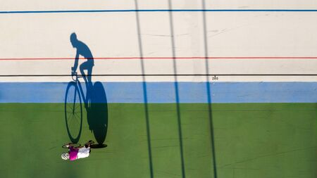 shadow of a cyclist training at a velodrome. preparation for professional competitions. Original creative shape top view 免版税图像