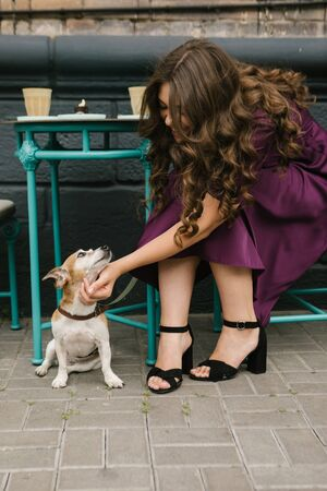 Elegant stylish woman petting small dog Jack russell terrier. Street cafe.