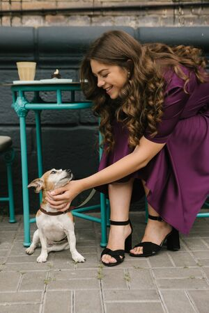 Dog and girl in street cafe. Beautiful woman in purple dress pettin small cute dog sitting under the table. Street cafe 免版税图像