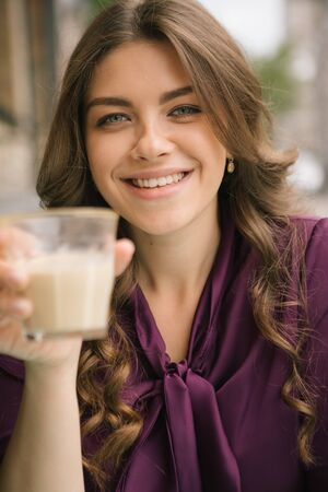 Smiling happy woman portrait with cup of Cappuccino. Beautiful long hair. Street cafe