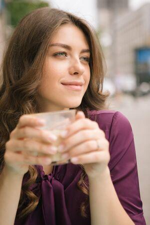 Dreamy beautiful woman in street cafe having coffee. Slavic beauty appearance. long hair