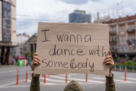 Funny inspiring text on sign. Party time motivation. Have fun. Outside protest banner message. I want to dance with somebody. Hand holding poster with call dancing and active sports. social motivation Archivio Fotografico