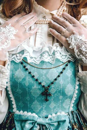 Beautiful woman in vintage blue dress. Cross. Elegant lady
