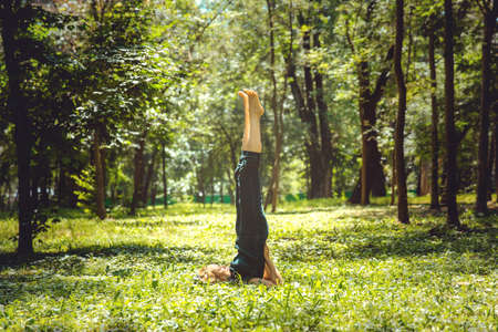 Salamba Sarvangasana. Yoga asanas in nature. Yoga poses everyday. Practicing young woman. Yoga in the park