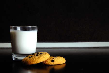 Goedemorgen. Ontbijtkoekjes en een glas melk. yoghurt. Zwarte achtergrond. zwart en wit Stockfoto