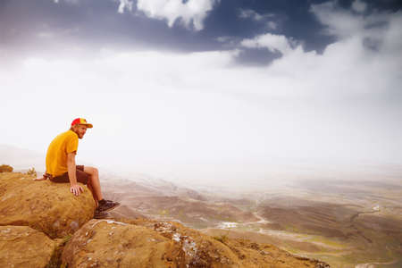 Young man on a rock in the mountains. View of the valley