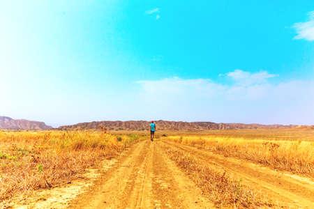 Young traveler guy walks wandering on hot savannah Stock fotó