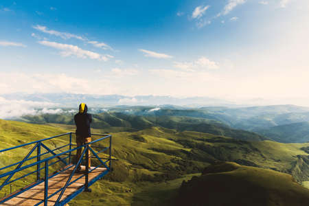 Young man in hiking adventure outfit stands on viewing platform or observation point over amazing epic valley looks around enjoying natural wonderadventure lifestyle extreme vacations green landscape. Reklamní fotografie