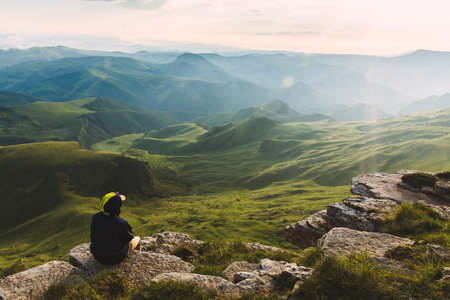 Travel man tourist sitting alone on the edge mountains over green valley adventure lifestyle extreme vacations green landscape