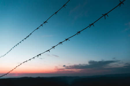 Barbed wire on the background of the sunrise in the mountains. Early morning purple Stock fotó