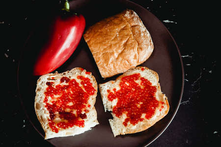 Fresh bread with butter and red caviar on a plate. Dark background