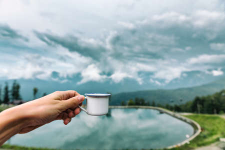 A small mug of tea in the hand. Mountains lake background. Travel. Nature
