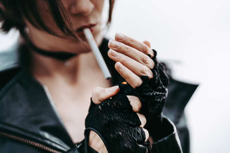 rock girl in a black leather jacket and gloves lights a cigarette. Smoking.