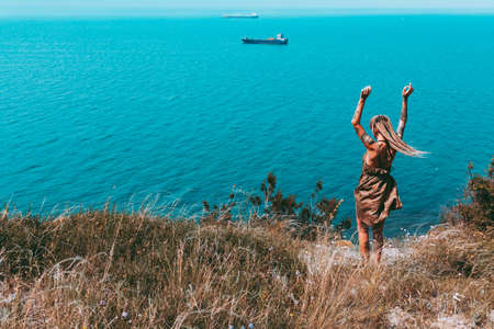 Beautiful slender tattooed woman with blonde dreadlocks in a dress rejoices on a hill. Sea View Travel and Vacation Beautiful landscape