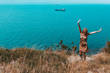 Beautiful slender tattooed woman with blonde dreadlocks in a dress rejoices on a hill. Sea View Travel and Vacation Beautiful landscape Stock Photo - 144046930