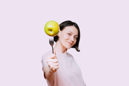 Young Woman holds in hand a fork with green apple on a light background. Healthy organic food for dieting woman concept