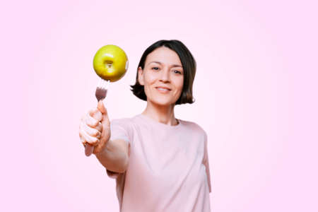 Young Woman holds in hand a fork with green apple on a light pink background. Healthy organic food for dieting woman concept