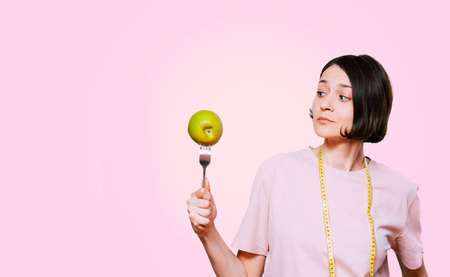 Woman holds in hand a fork with green apple and tape measure on a light pink background. Healthy organic food for dieting woman concept Stockfoto