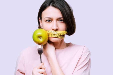 Woman holds in hand a fork with green apple covers her mouth with an tape measure on a light background. Healthy organic food for dieting woman concept