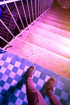 Psychedelic pink purple photo of legs in sneakers near the stairs down. Fear of going forward. A long hard way. Conceptual