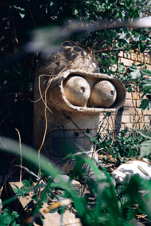 The concrete stone head of a Bender robot from the Futurama cartoon stands among green plants Stockfoto