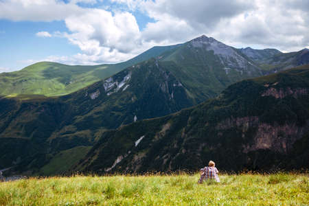 Traveler hiking alone man sits on a green meadow in front of a mountain landscape. Summer time. Travel. Georgia. adventure, active, lifestyle, vacations, outdoor Stockfoto