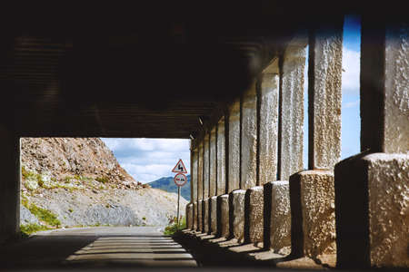 Mountain road . Inside the tunnel with columns. Road sign