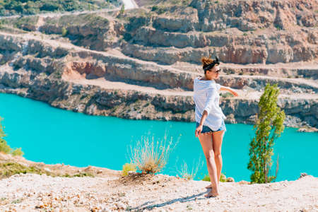 A slender girl in a white shirt dancing alone by the sandy career. Against the background of mountains and a blue azure lake. Georgia landscape