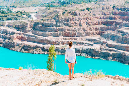A slender girl in a white shirt walks alone be the sandy career. Against the background of mountains and a blue azure lake. Georgia summertime Stockfoto