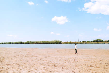A melancholy girl in a white shirt walks alone by the river Bank. Small figure walks along the sand