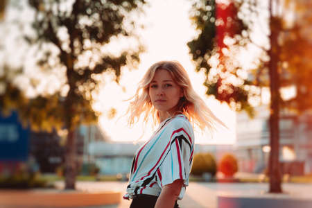 Attractive blonde girl smiling at sunset. Hipster lifestyle