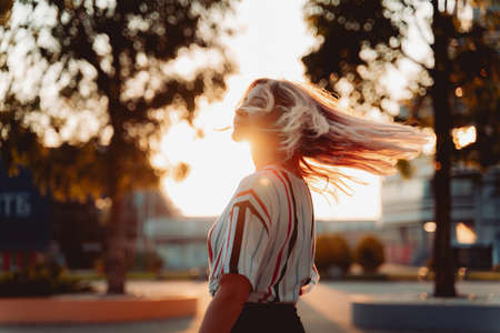 Attractive blonde girl smiling at sunset. Happy Hipster lifestyle Stockfoto