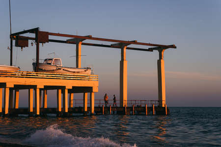 Two people stand on a pier at sunset. Motor boat at sea